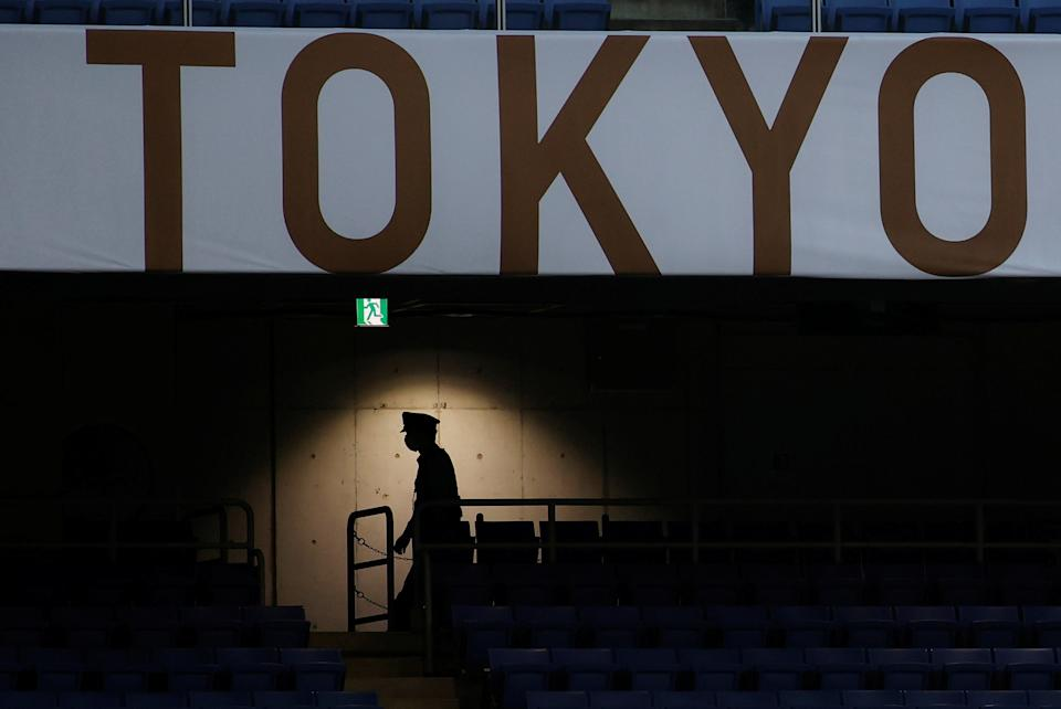 Tokyo 2020 Olympics - Soccer Football - Men - Group D - Ivory Coast v Saudi Arabia - International Stadium Yokohama, Yokohama, Japan - July 22, 2021. A member of staff wearing a protective face mask is seen in the stand during the match REUTERS/Phil Noble     TPX IMAGES OF THE DAY