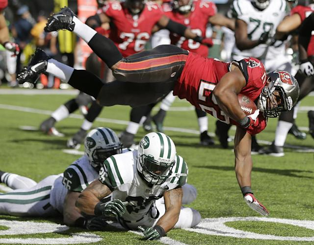 Tampa Bay Buccaneers running back Doug Martin (22) flies after being hit by New York Jets outside linebacker DeMario Davis (56) and strong safety Dawan Landry (26) in the second half of an NFL football game, Sunday, Sept. 8, 2013, in East Rutherford, N.J. (AP Photo/Mel Evans)