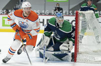 Edmonton Oilers center Connor McDavid (97) and Vancouver Canucks goaltender Thatcher Demko (35) look for the puck during the third period of an NHL hockey game Tuesday, Feb. 23, 2021, in Vancouver, British Columbia. (Jonathan Hayward/The Canadian Press via AP)
