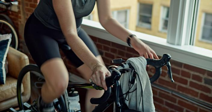 A caucasian woman in her 30s works out on a bike trainer in an urban apartment.