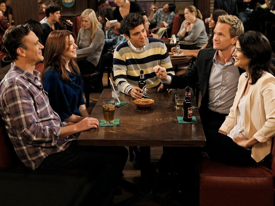"""From left: Jason Segel, Alyson Hannigan, Josh Radnor, Neil Patrick Harris, and Cobie Smulders sitting at a table on season eight, episode four of """"How I Met Your Mother."""""""