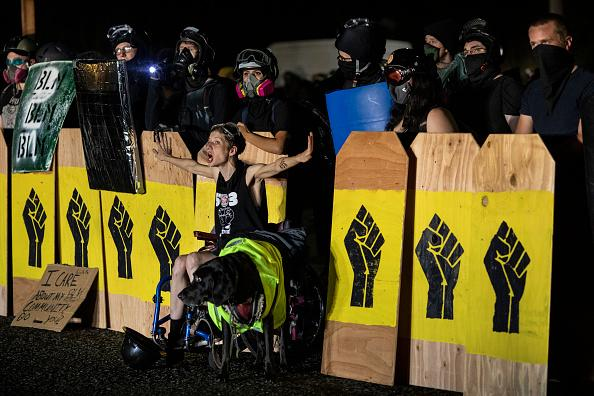 A handicapped protester screams at police during a standoff at a Portland precinct on August 15. Source: Getty