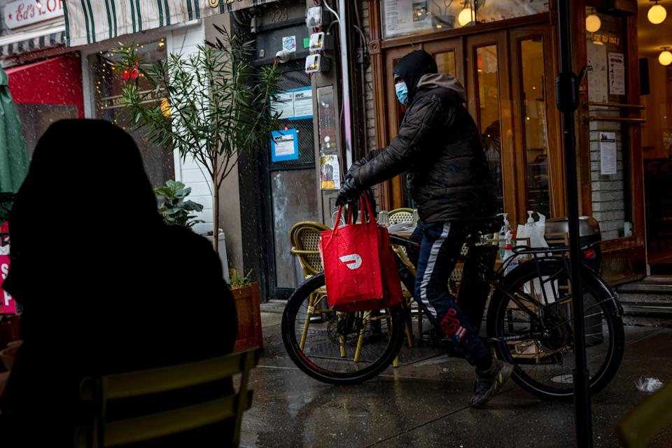 NEW YORK, NEW YORK - DECEMBER 09: A DoorDash delivery driver riding a bicycle picks up food from Jack's Wife Freda during the first snow of the season on December 09, 2020 in New York City. The pandemic continues to burden restaurants and bars as businesses struggle to thrive with evolving government restrictions and social distancing plans which impact keeping businesses open yet challenge profitability. (Photo by Alexi Rosenfeld/Getty Images)