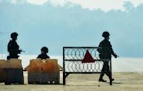 Soldiers keep watch along a blockaded road in Naypyidaw, as Myanmar's generals appear in firm control after a surgical coup that saw democracy heroine Aung San Suu Kyi detained