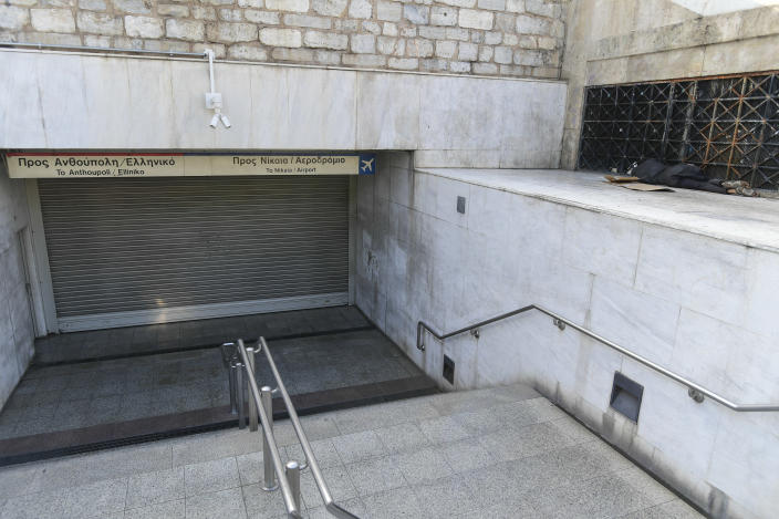 A homeless man sleeps outside a closed entrance of Syntagma metro station during a 24-hour labour strike in Athens, Thursday, June 10, 2021. Greece's biggest labor unions stage a 24-hour strike to protest a draft labor bill being debated in parliament, which workers say will erode their rights. (AP Photo/Michael Varaklas)