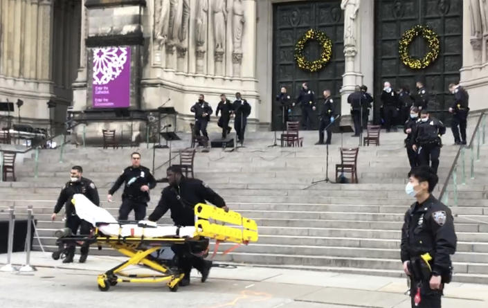 Emergency medical personnel pull a stretcher up to the scene of a shooting at the Cathedral Church of St. John the Divine, Sunday, Dec. 13, 2020, in New York. A man was shot by police after shots rang out at the end of a Christmas choral concert on the steps of the Manhattan cathedral Sunday afternoon. The shooting happened just before 4 p.m. at the church which is the mother church of the Episcopal Diocese of New York and seat of its bishop. (AP Photo/Ted Shaffrey)