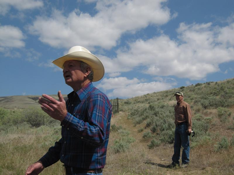 Max Benitz, left, gestures while talking about the McWhorter Ranch in Benton County, northeast of Prosser, Wash. on May 18, 2012, while Mike Livingston of the Washington Department of Fish and Wildlife listens. The descendants of the man who settled the ranch in 1903 are putting it up for sale, and Benitz is among those hoping it can be preserved for public use. (AP Photo/Shannon Dininny)