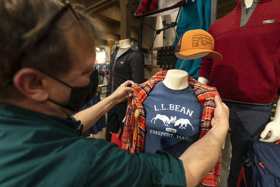 Will Foster, a worker at the L.L. Bean flagship retail store, adjusts display clothing on a mannequin, Thursday, March 18, 2021, in Freeport, Maine. Maine-based retailer L.L. Bean saw the best sales in nearly a decade during pandemic. Officials say the Freeport-based retailer started its fiscal year with store closings and worries about survival but the company weathered the turbulent times to revenue growth of 5%. (AP Photo/Robert F. Bukaty)