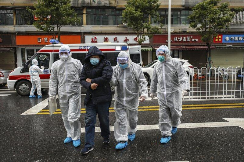 Medical professionals in protective gear help a patient in Wuhan. Source: AP