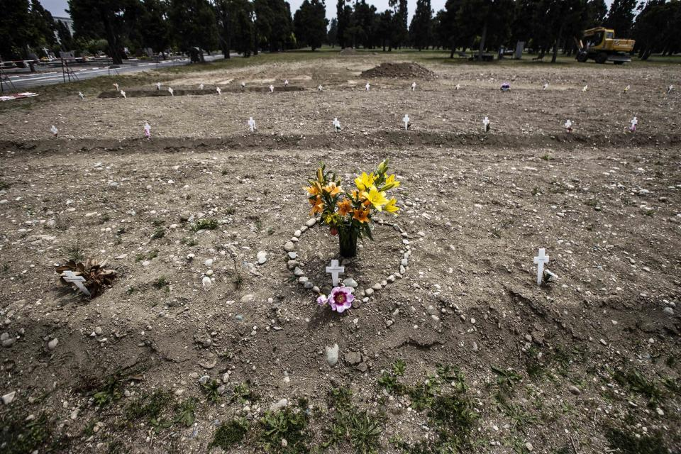 FILE - In this May 8, 2020 file photo, flowers and stones placed in the shape of a heart are laid on a burial site as white crosses are scattered at the Campo 81, an area created to host COVID-19 victims, at the Maggiore cemetery in Milan, Italy. Italy on Sunday Dec. 13, 2020 eclipsed Britain to become the nation with the worst official coronavirus death toll in Europe. Italy, where the continent's pandemic began, registered 484 COVID-19 deaths in one day, one of its lowest one-day death counts in about a month. (AP Photo/Luca Bruno, file)