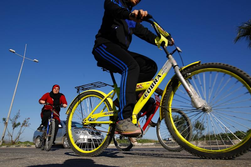 Amneh Salman (left) ride with her friends on a road in in Beit Hanun (AFP Photo/Mohamed Abed)