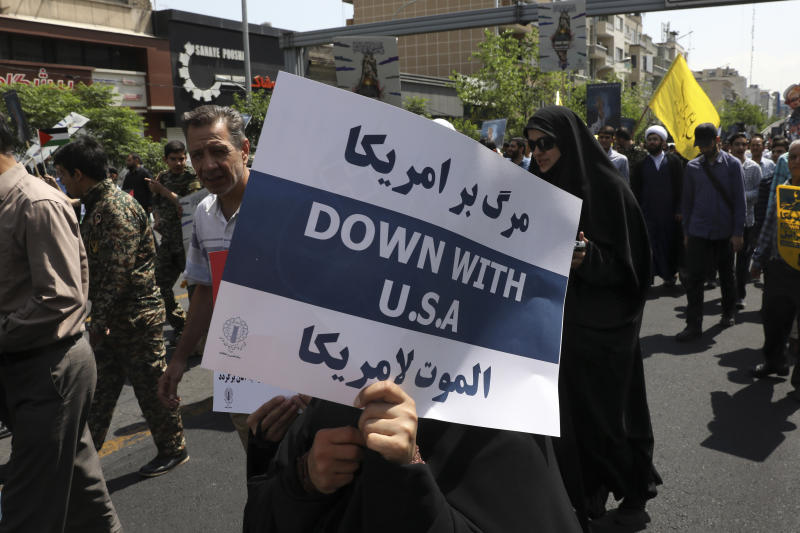 FILE - In this May 31, 2019 file photo, a demonstrator holds an anti-U.S. placard during the annual Quds, or Jerusalem Day rally in Tehran, Iran. The top line on the placard in Farsi translates to, Death to America, and the bottom line on the placard in Arabic translates to, Death to America. (AP Photo/Vahid Salemi)