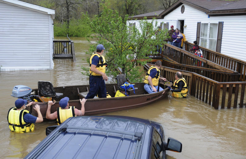 CORRECTS DATE TO APRIL 7 Firefighters rescue a family from their home, surrounded by floodwaters, in a mobile home park in Pelham, Ala., on Monday, April 7, 2014. Overnight storms dumped torrential rains in central Alabama, causing flooding across a wide area. (AP Photo/Jay Reeves)