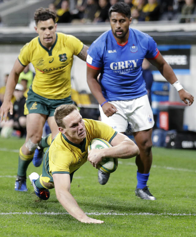 Australia's Dane Haylett-Petty, bottom, dives over to score a try against Samoa during their rugby union test match in Sydney, Saturday, Sept. 7, 2019. (AP Photo/Rick Rycroft)