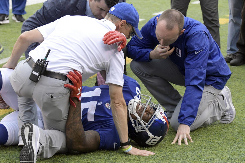 Trainers take a look at New York Giants wide receiver Brandon Marshall after he went down making a catch last October. (AP)