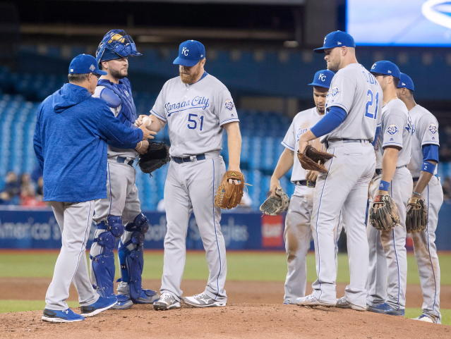 Kansas City Royals relief pitcher Blaine Boyer (51) hands the ball to his manager Ned Yost in the sixth inning of the first game of a baseball doubleheader against the Toronto Blue Jays in Toronto on Tuesday April 17, 2018. (Fred Thornhill/The Canadian Press via AP)