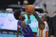 Charlotte Hornets forward Jalen McDaniels, left, drives to the basket against Atlanta Hawks center Clint Capela, right, during the third quarter of an NBA basketball game in Charlotte, N.C., Sunday, April 11, 2021. (AP Photo/Nell Redmond)