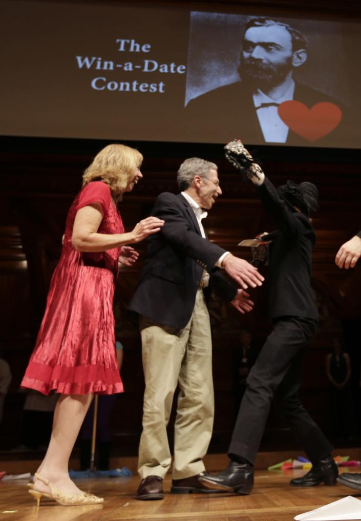 """2007 Nobel Prize laureate in Economics Eric Maskin, center, embraces a woman after a drawing for a """"Win a Date with a Nobel Laureate"""" contest during a performance at the Ig Nobel Prize ceremony at Harvard University, in Cambridge, Mass., Thursday, Sept. 20, 2012. The Ig Nobel prize is an award handed out by the Annals of Improbable Research magazine for silly sounding scientific discoveries that often have surprisingly practical applications. (AP Photo/Charles Krupa)"""