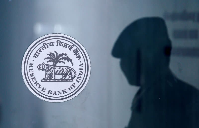 FILE PHOTO: A security guard's reflection is seen next to the logo of the Reserve Bank Of India (RBI) at the RBI headquarters in Mumbai