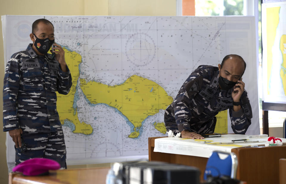 Indonesian military officials speak on phone in front of a map of the location where the Indonesian Navy submarine KRI Nanggala that went missing while participating in a training exercise on Wednesday, at a command at Ngurah Rai Airport, Bali, Indonesia on Friday, April 23, 2021. Rescuers continued an urgent search Friday for an Indonesian submarine that disappeared two days ago and has less than a day's supply of oxygen left for its crew.(AP Photo/Firdia Lisnawati)