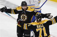 Boston Bruins' Craig Smith (12) celebrates his goal with Taylor Hall (71) during the first period of an NHL hockey game against the Buffalo Sabres, Saturday, May 1, 2021, in Boston. (AP Photo/Michael Dwyer)