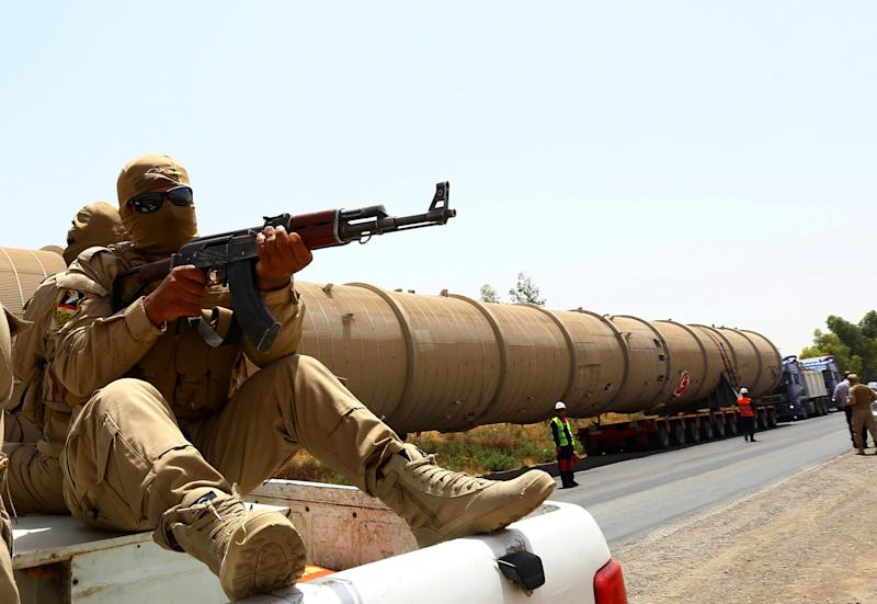 A section of an oil refinery is guarded as it is brought on a lorry to the Kawergosk Refinery, some 20 kilometres east of Arbil, the capital of the autonomous Kurdish region of northern Iraq, on July 14, 2014