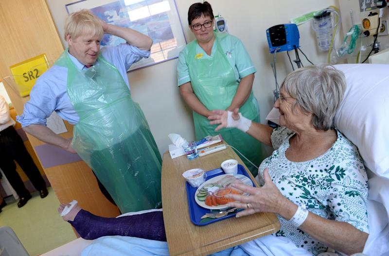 Prime Minister Boris Johnson serves food to Wenona Pappin, 70, during a visit to Torbay Hospital in Devon after he welcomed a review into hospital food following the deaths of six people due to a listeria outbreak.