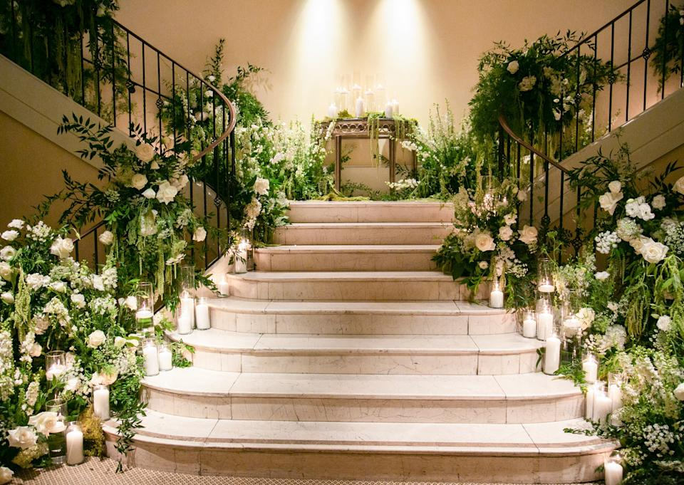 Lush romantic florals and candles up the double staircase to welcome guests by Ixora Floral Studio.