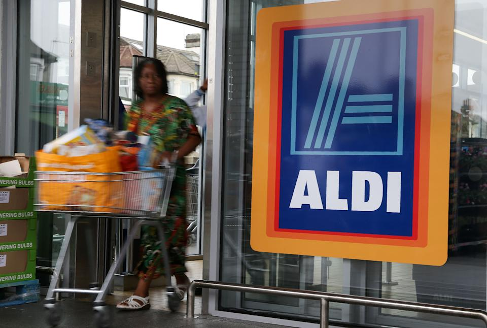 A woman pushes a shopping trolley past an Aldi logo. Source: Getty Images