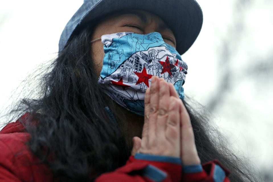 A woman closes her eyes as she prays during a vigil and rally against Asian hate crimes, Friday, March 26, 2021, at Chicago's Horner Park. The event is organized by local Chicago organizations led by Asian Americans and Pacific Islanders. (AP Photo/Shafkat Anowar)