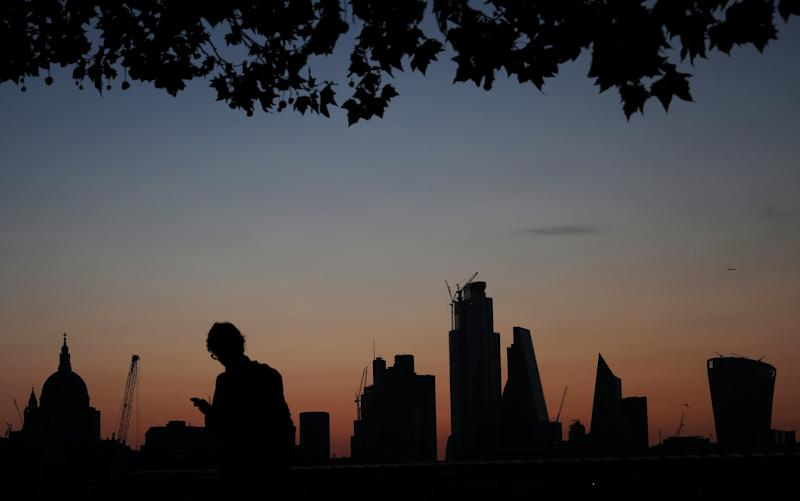 A man walks past the city of London financial district as dawn breaks in London, Britain August 20, 2019. REUTERS/Hannah McKay