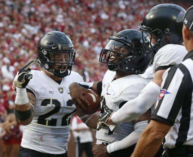 Army quarterback Kelvin Hopkins Jr. (8) celebrates with teammates Calen Holt (22) and Camden Harrison, right, after scoring against Oklahoma in the first half of an NCAA college football game in Norman, Okla., Saturday, Sept. 22, 2018. (AP Photo/Sue Ogrocki)
