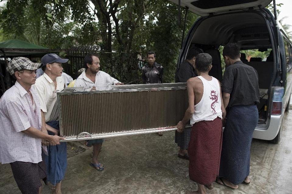 Social welfare society workers load a casket into a van ahead of a funeral in Thingangyun township (AFP Photo/Nicolas Asfouri)