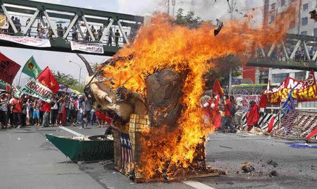 Protesters burn an effigy of Philippines' President Benigno Aquino near Batasang Pambansa, where Aquino will address the joint session of Congress delivering his last State of the Nation address, in Quezon city, Metro Manila, in the Philippines July 27, 2015. REUTERS/Lorgina Minguito