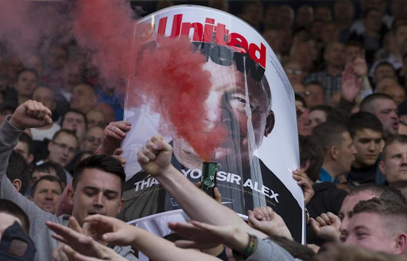 Manchester United supporters hold up a smoke bomb in front of a poster of manager Sir Alex Ferguson during their manager's last game in charge of the team, their English Premier League soccer match away at West Bromwich Albion at The Hawthorns Stadium, West Bromwich, England, Sunday May. 19, 2013. (AP Photo/Jon Super)