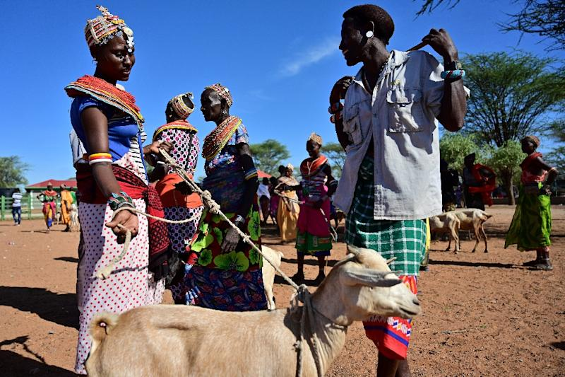A traditional Samburu man haggles for a goat with a woman from the same community at Merille livestock market (AFP Photo/TONY KARUMBA)