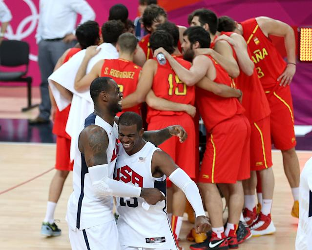LONDON, ENGLAND - AUGUST 12: LeBron James #6 of the United States and team mate Chris Paul #13 of the United States celebrate winning the Men's Basketball gold medal game between the United States and Spain as Spain form a huddle on Day 16 of the London 2012 Olympics Games at North Greenwich Arena on August 12, 2012 in London, England. The United States won the match 107-100. (Photo by Streeter Lecka/Getty Images)
