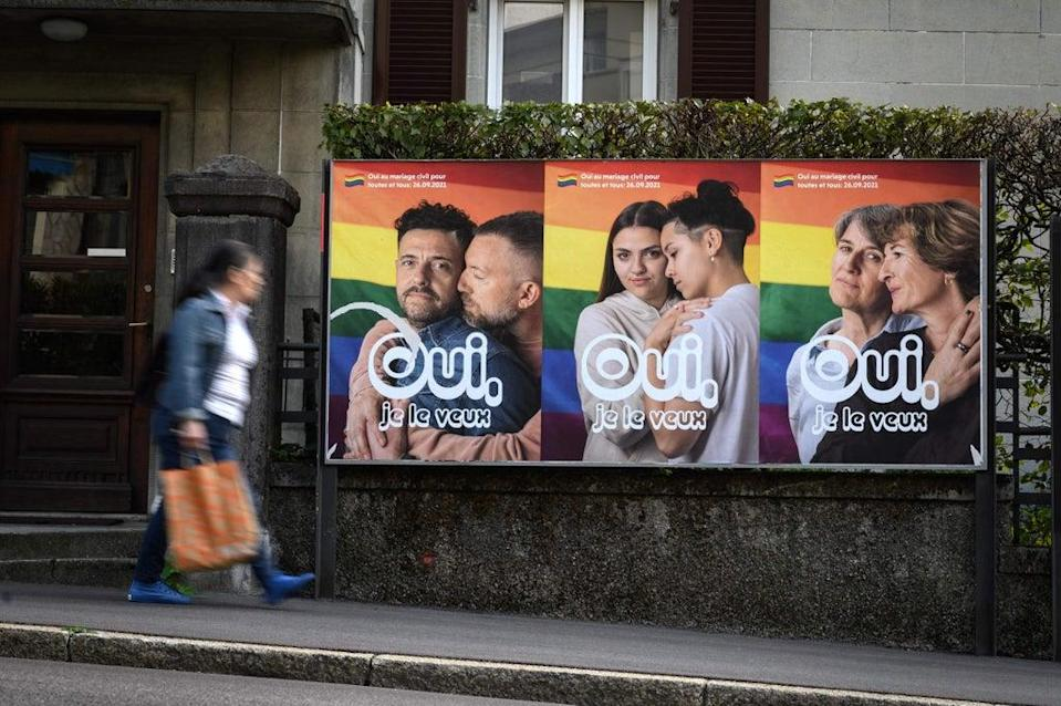 A woman walks past an electoral poster in the town of Lausanne, Switzerland ahead of a nationwide vote on  same-sex marriage   (AFP via Getty Images)