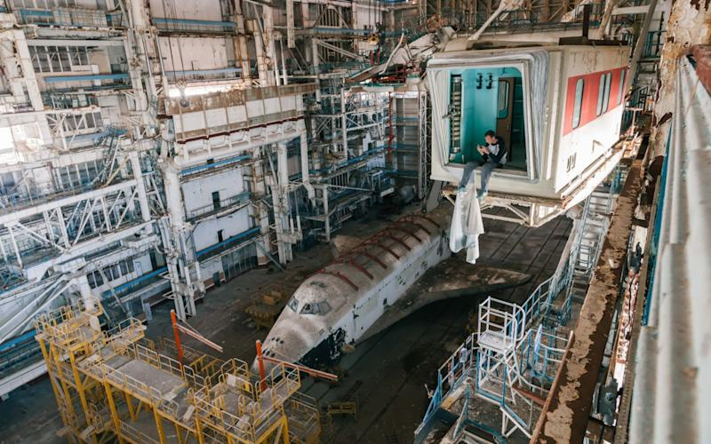 An urban explorer admires the last remaining Soviet space shuttle in a hangar at the Baikonur cosmodrome in Kazakhstan - Andrei Ghilan / mediadrumimages.