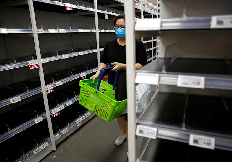 A woman wearing a protective mask passes empty shelves of instant noodles and canned food as people stock up on food supplies after Singapore raised coronavirus outbreak alert level to orange, at a supermarket in Singapore on 8 February, 2020. (PHOTO: Reuters)