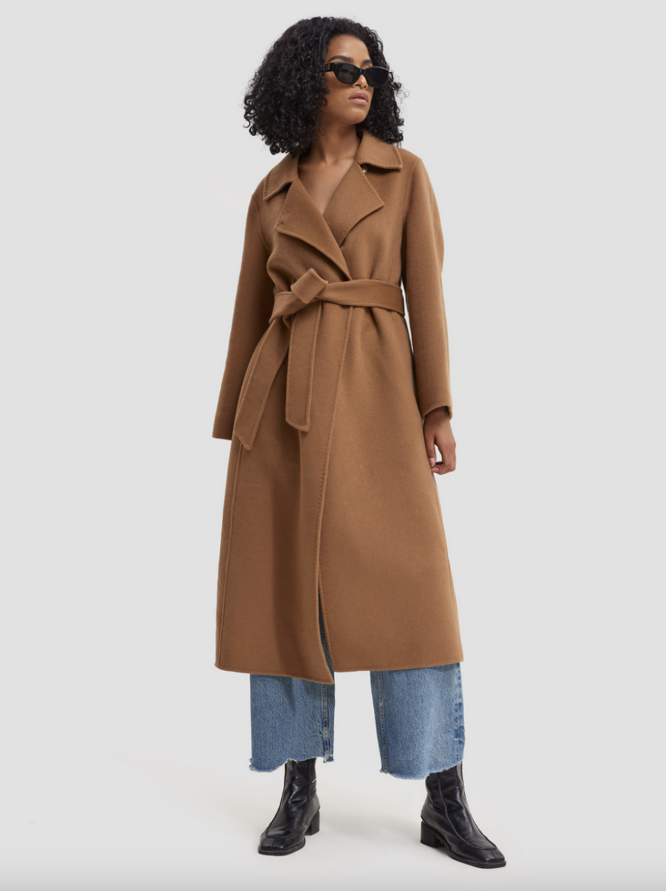 black model with curly hair and sunglasses wearing black boots, blue jeans and camel Earth Tone Belted Wool Coat
