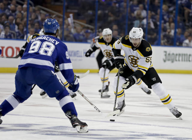 Boston Bruins center Tim Schaller, right, makes a move to get around Tampa Bay Lightning defenseman Mikhail Sergachev (98) during the first period of Game 2 of an NHL second-round hockey playoff series Monday, April 30, 2018, in Tampa, Fla. (AP Photo/Chris O'Meara)