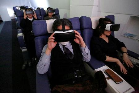 "Guests wearing virtual reality (VR) goggles are seen at the ""First Airlines"", virtual first-class airline experience facility in Tokyo, Japan February 14, 2018. Picture taken February 14, 2018.  REUTERS/Toru Hanai"