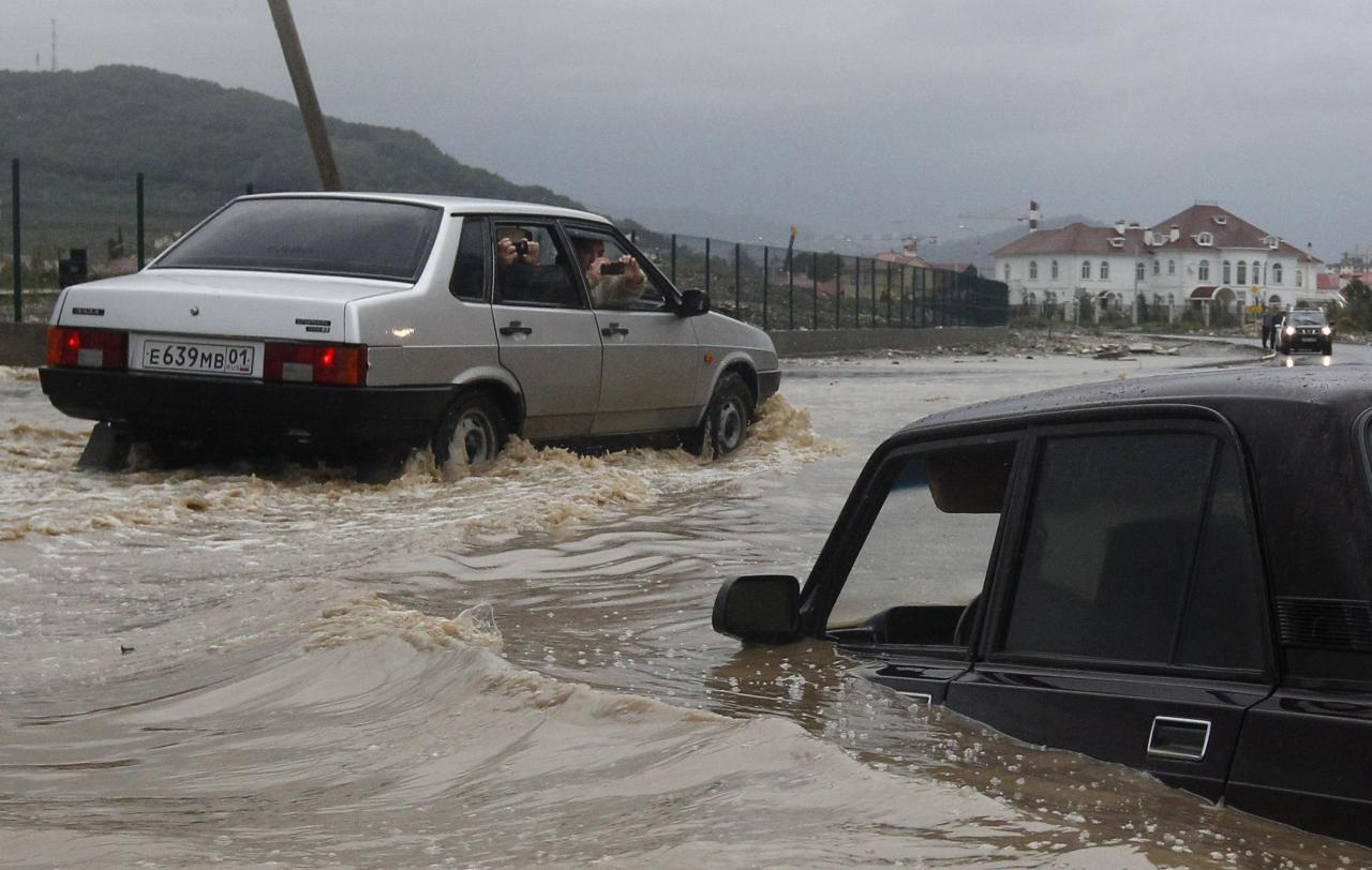 People take pictures of car stranded in floodwaters along a flooded street in Sochi