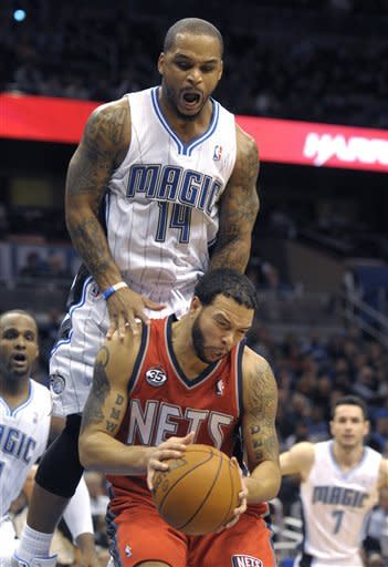 New Jersey Nets guard Deron Williams is fouled by Orlando Magic guard Jameer Nelson (14) as Orlando's Glen Davis, left, and J.J. Redick watch during the first half of an NBA basketball game in Orlando, Fla., Thursday, Dec. 29, 2011.(AP Photo/Phelan M. Ebenhack)
