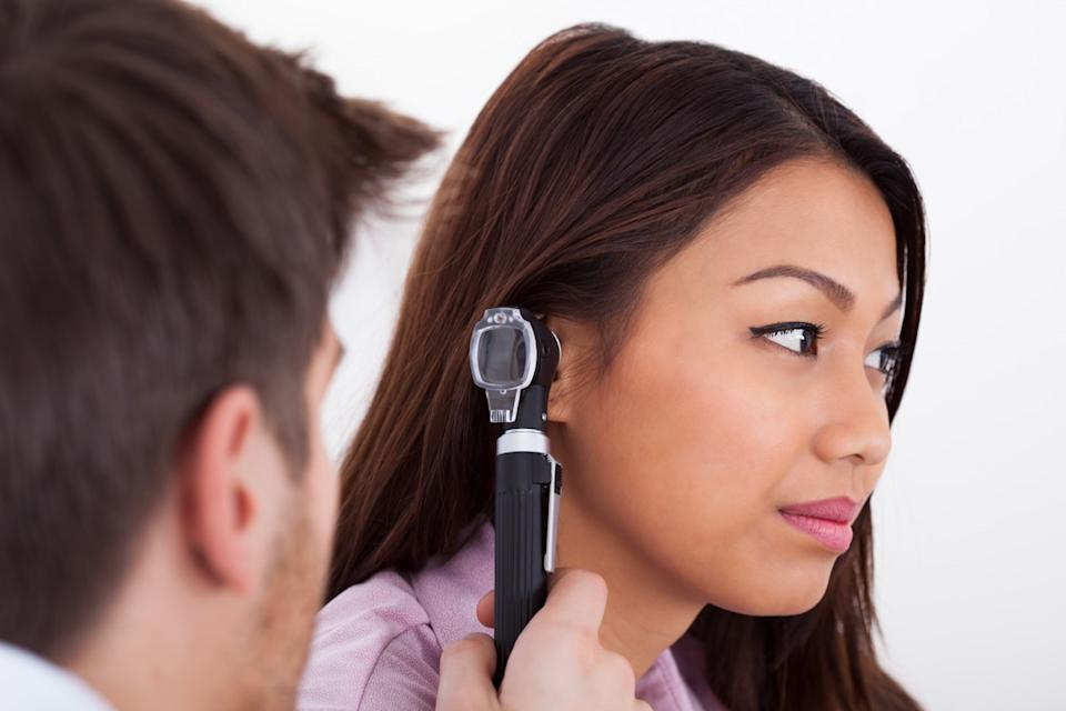 male doctor examining patient's ear with otoscope in clinic