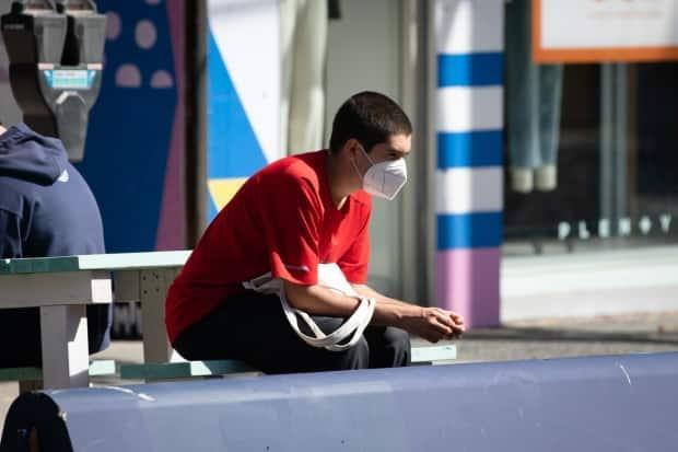 A masked young man seated at an outdoor seating area in Vancouver, B.C. during the COVID-19 pandemic on Tuesday, Sept. 7, 2021.  (Maggie MacPherson/CBC - image credit)
