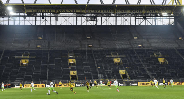 FILE - In this Feb. 18, 2017 file photo, players challenge for the ball in front of the empty south tribune because of a ban following fan trouble during the German Bundesliga soccer match between Borussia Dortmund and VfL Wolfsburg at Germany's biggest stadium in Dortmund, Germany. Bundesliga will now restart on May 16, 2020 when Dortmund will play the derby against Schalke at home without spectators due to the coronavirus outbreak. (AP Photo/Martin Meissner, file)