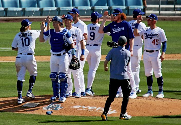 The Dodgers celebrate a 1-0 victory over the Nationals in the home opener.