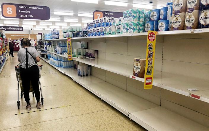 Toilet roll shelves near empty at a supermarket in London - Eddie Mulholland